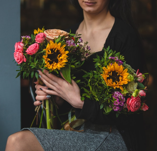 Una donna elegante con due bouquet di rose e girasoli
