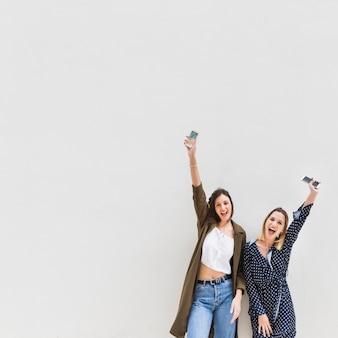 Una donna emozionante alla moda due che alza il loro cellulare della tenuta della mano contro fondo bianco