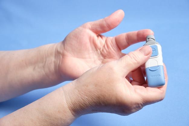 Una donna fa un esame del sangue per lo zucchero, su uno spazio blu. spazio per il testo