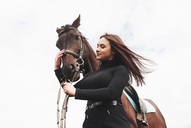 Una donna felice comunica con il suo cavallo preferito. la donna ama gli animali e l'equitazione