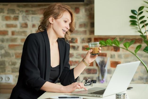 Una donna felice con le parentesi graffe che lavorano in remoto su un computer portatile in una cucina. una signora con un caffè che discute di un progetto con i colleghi in una videoconferenza a casa.