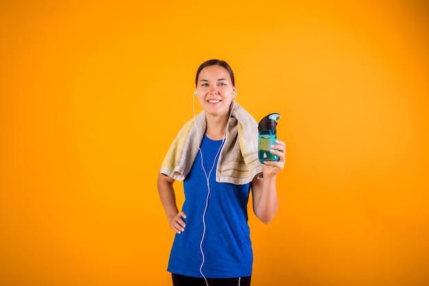 Una donna felice in uniforme sportiva con un asciugamano e una bottiglia d'acqua su una parete arancione con una copia dello spazio