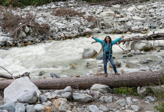 Una donna fotografa un fiume tra le montagne del caucaso settentrionale.