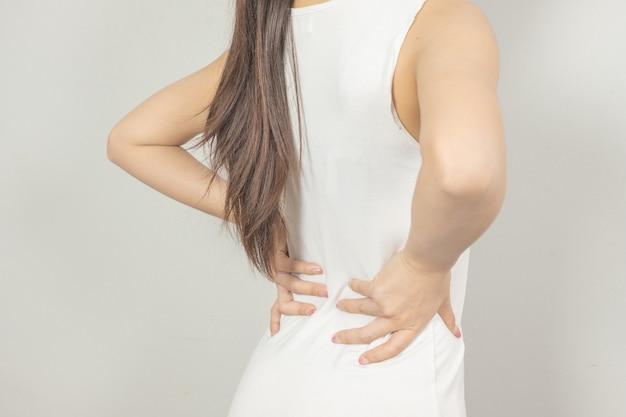 Una donna gli teneva la mano dietro di sé con mal di schiena. concetto di assistenza sanitaria