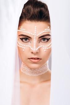 Una donna guarda fuori da sotto il velo e guarda la telecamera. foto verticale di moda