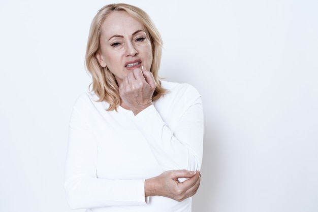 Una donna ha un dolore nel suo braccio su sfondo bianco.
