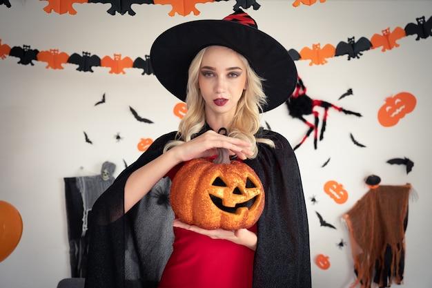 Una donna in abbigliamento strega tenendo la festa di zucca