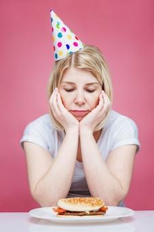 Una donna in abiti domestici e un cappello festivo siede triste davanti a un hamburger su un piatto. compleanno solitario in periodo di isolamento sullo sfondo del coronavirus. sfondo rosa. verticale.