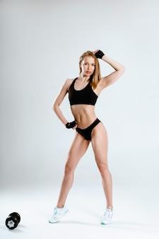 Una donna in abiti sportivi neri pone, mostrando i suoi muscoli e addominali su uno sfondo bianco.