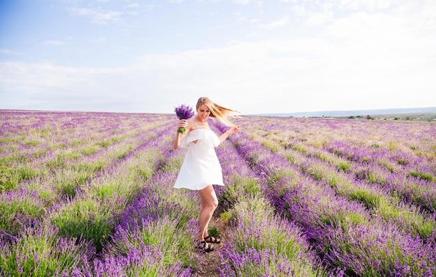 Una donna in abito bianco con un mazzo di fiori è un campo di lavanda in fiore