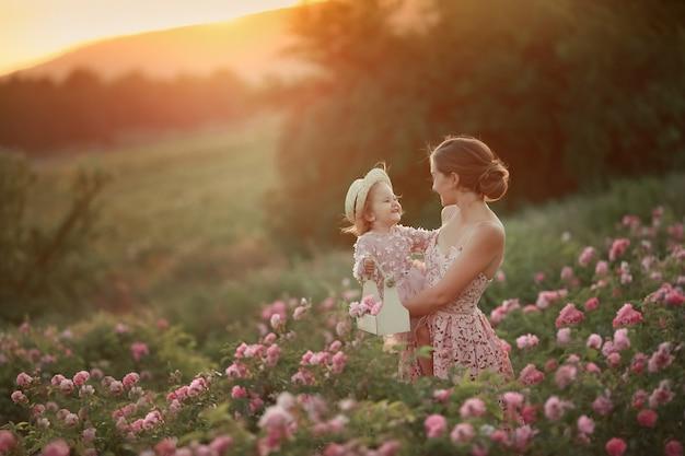 Una donna in abito retrò con sua figlia di 5 anni che cammina in primavera in un campo con rose