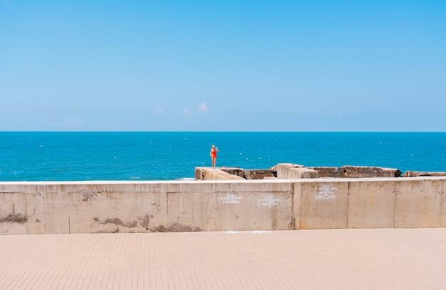 Una donna in costume da bagno rosso e il mare