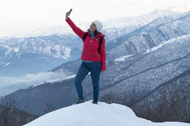 Una donna in giacca rossa, jeans e maglione blu è in montagna
