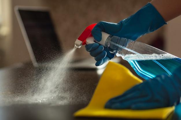 Una donna in guanti mette un antisettico sul tavolo e lo pulisce con un tovagliolo. mezzi per prevenire la diffusione di virus e malattie, incluso covid-19. pulizia dell'appartamento