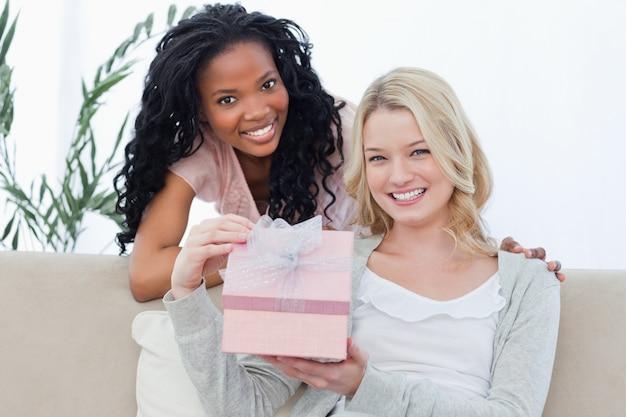 Una donna in possesso di un regalo è sorridendo alla telecamera con la sua amica