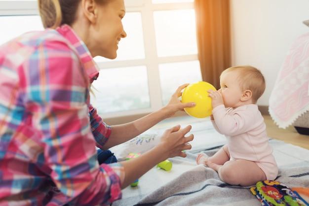 Una donna in salotto gioca con il suo bambino piccolo.