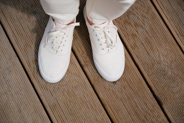 Una donna in scarpe da ginnastica si trova sul marciapiede o sul marciapiede in legno