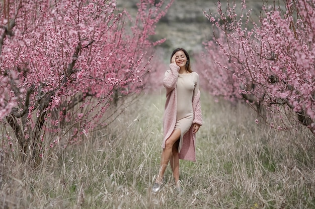 Una donna in un abito lungo e stretto cammina lungo una fila tra i peschi con un albero in fiore