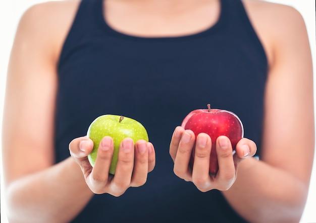 Una donna in un vestito di idoneità sta tenendo un verde e un rosso mela concetto sano di cibo.