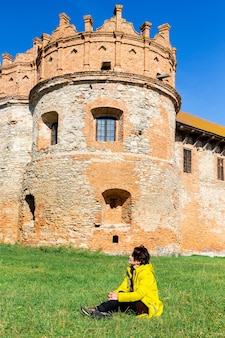 Una donna in una giacca gialla vicino all'antico castello della torre