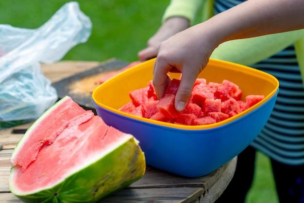 Una donna in una giornata calda offre pezzi di anguria a fette.
