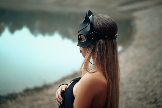 Una donna in una maschera di gatto nero si trova sullo sfondo della natura.
