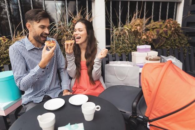 Una donna incinta con un uomo è seduta al tavolo di un caffè.