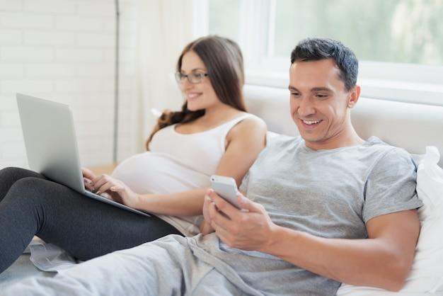 Una donna incinta e un uomo sono distesi sul letto.