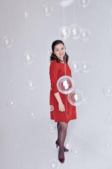 Una donna incinta in un abito rosso .. concetto di maternità, festa della famiglia, festa della mamma, fecondazione in vitro