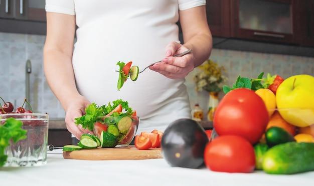 Una donna incinta mangia frutta e verdura