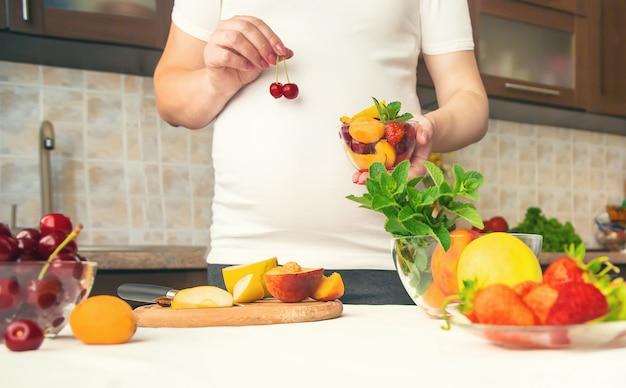 Una donna incinta mangia frutta