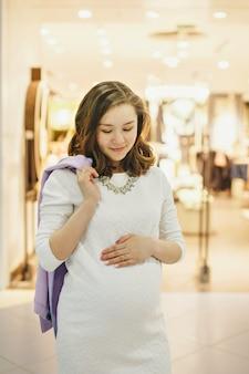 Una donna incinta si accarezza lo stomaco.