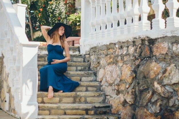 Una donna incinta si siede sui gradini di pietra di un edificio storico. turista in gita. ragazza in vacanza