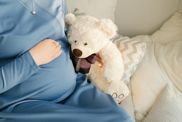 Una donna incinta tiene una mano sul suo stomaco e accanto ad essa un orsetto di peluche