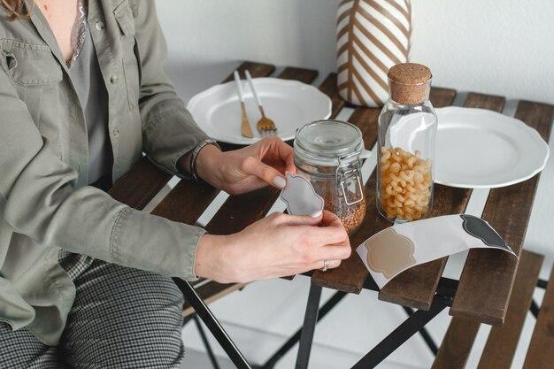 Una donna incolla un adesivo per l'iscrizione su un barattolo di cereali.