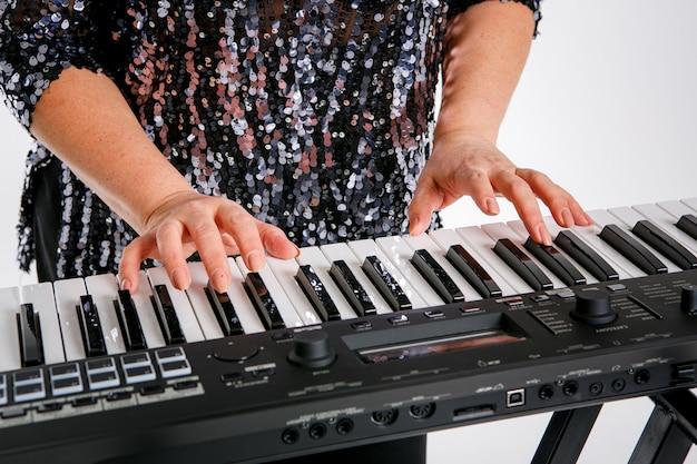 Una donna indossa una camicia lucida e posa con una tastiera di pianoforte. isolato su bianco
