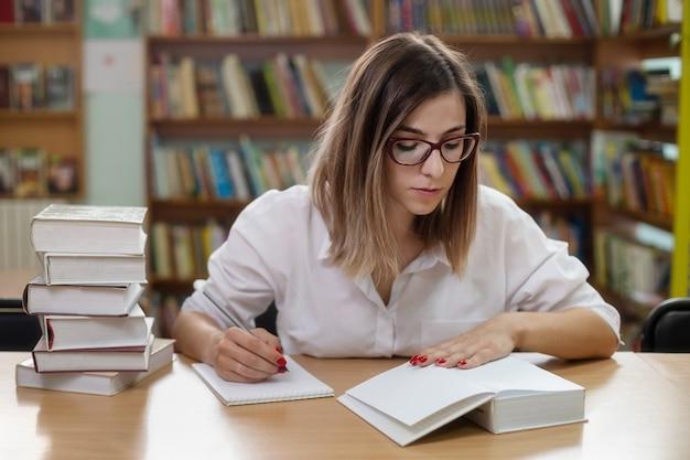 Una donna intelligente con gli occhiali che studia in biblioteca con i libri