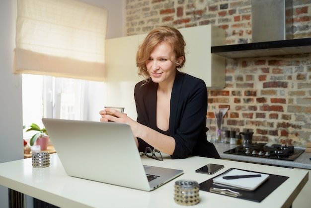 Una donna lavora a distanza su un laptop in cucina. una ragazza felice tiene una tazza di caffè ascoltando il rapporto di un collega in una videoconferenza a casa.