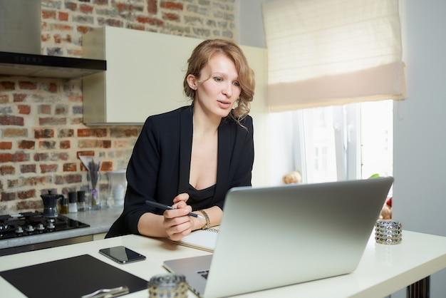 Una donna lavora a distanza su un laptop in cucina. una ragazza seria che fa appunti sul quaderno durante il rapporto di un collega durante una videoconferenza a casa.