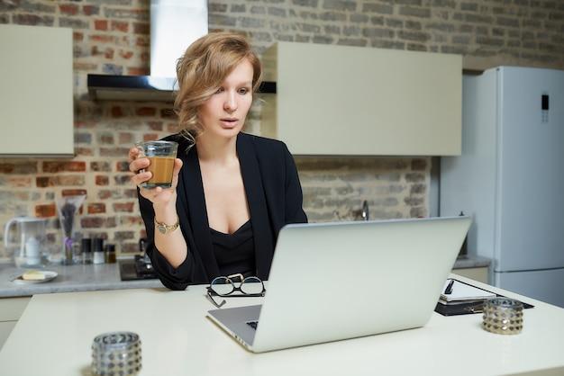 Una donna lavora a distanza su un laptop nella sua cucina. una ragazza discute con i suoi colleghi su un briefing aziendale online a casa. una signora tiene un bicchiere di caffè preparando per una lezione su una videochiamata.