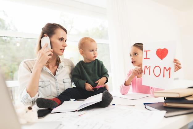 Una donna lavora e si prende cura dei bambini allo stesso tempo.