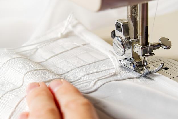 Una donna lavora su una macchina da cucire. sarta cuce tende bianche, vista ravvicinata.