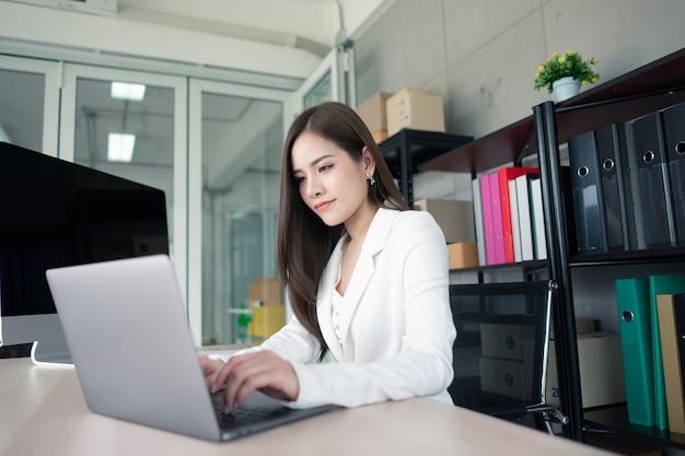Una donna lavoratrice in abito bianco sta lavorando in ufficio.