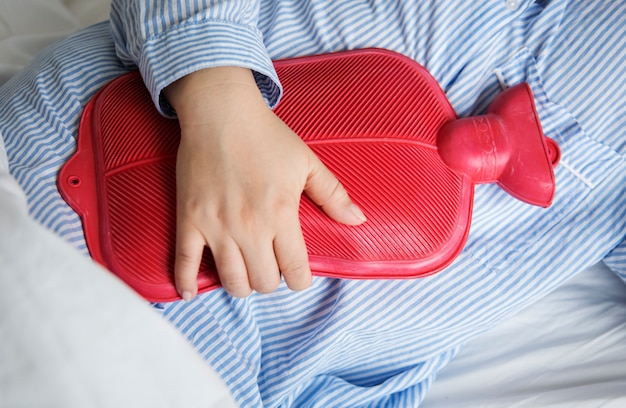 Una donna nel dolore in possesso di una bottiglia di acqua calda