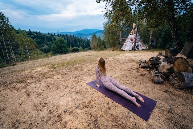 Una donna pratica yoga al mattino in un parco all'aria aperta.