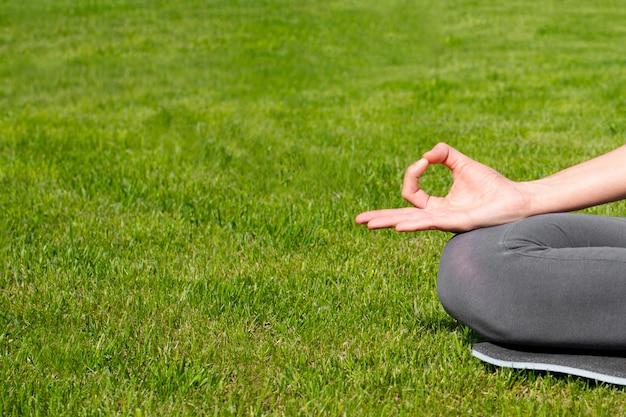 Una donna pratica yoga all'aperto sull'erba. salute mentale, riduzione dell'ansia, pace interiore