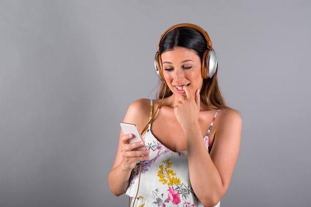 Una donna preoccupata che ascolta la musica e che utilizza il suo smartphone