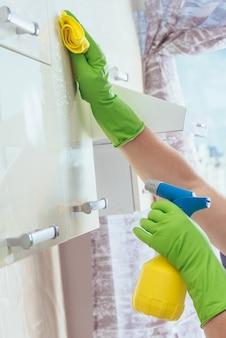 Una donna pulisce con un panno giallo l'armadio della cucina