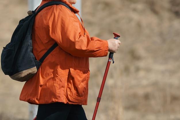 Una donna sconosciuta adulta in una passeggiata è impegnata nella camminata scandinava.