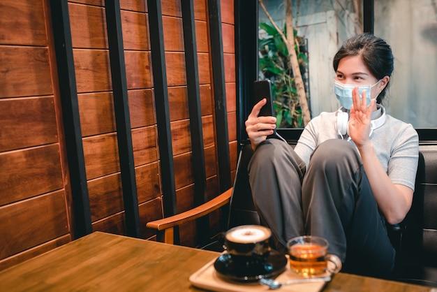 Una donna sedeva in una caffetteria con le cuffie che suonavano al telefono e una mascherina medica per proteggere covid-19.